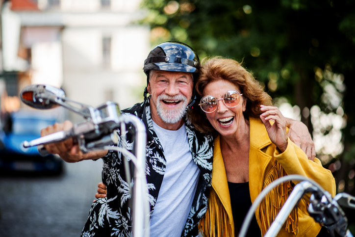 A cheerful senior couple travellers with motorbike in town.